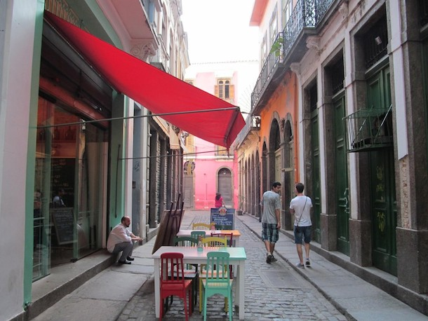 A narrow cobbled street in downtown Rio , with tables and chairs on the street