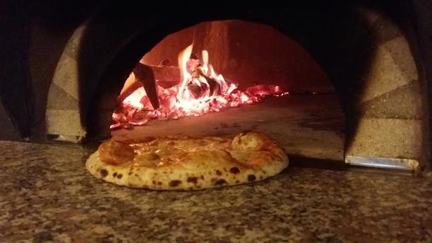 A pizza going into the wood-fired oven